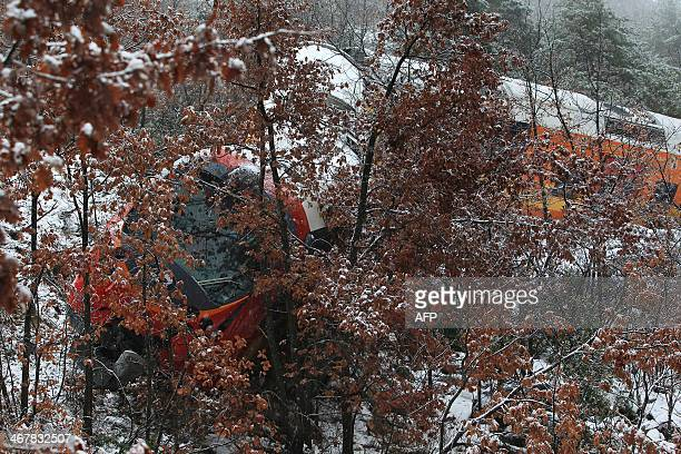 Photo taken on February 8 2014 shows the wreckage of a passenger train near DignelesBains in the French Alps after it derailed Two women were killed...