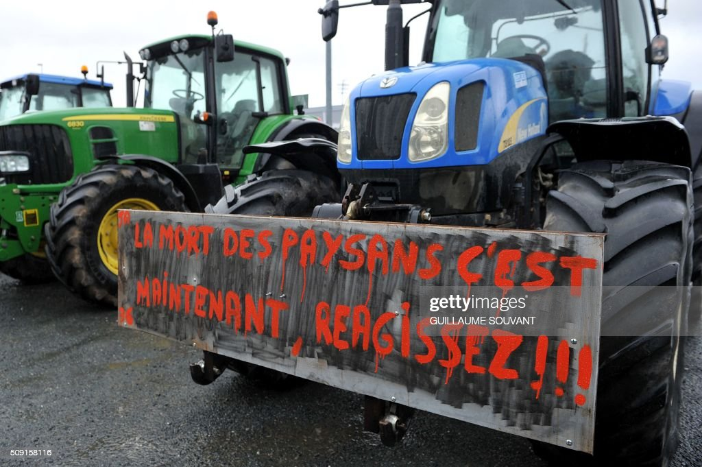A photo taken on February 9, 2016 shows a placard hung on a tractor which translate as 'The death of the farmers is now, react' during a protest by French farmers against the falling prices of agricultural products in Chateauroux, center France. / AFP / GUILLAUME SOUVANT