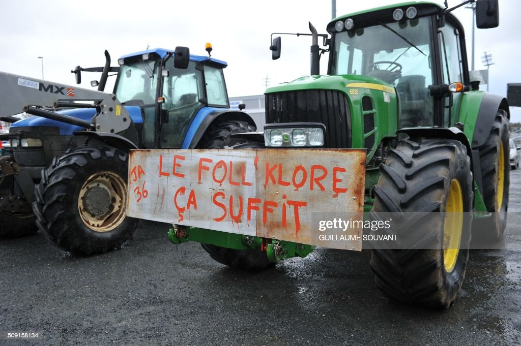 A photo taken on February 9, 2016 shows a placard hung on a tractor which translate as 'Foll'klore is enough' using a play on words on the name of French Minister of Agriculture Stephane Le foll, during a protest by french farmers against the falling prices of agricultural products in Chateauroux, center France. / AFP / GUILLAUME SOUVANT
