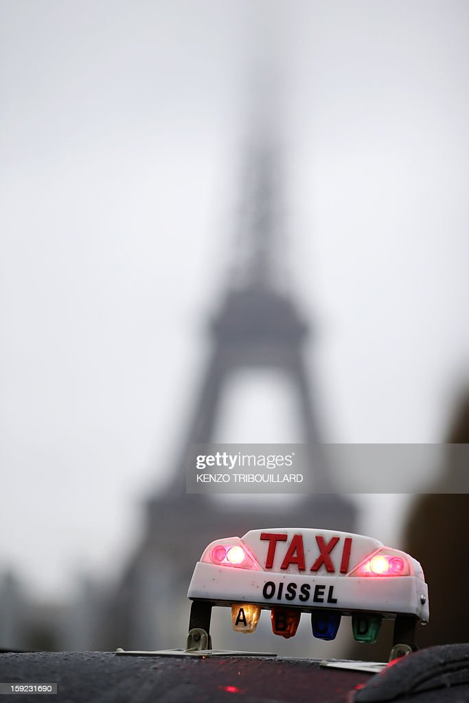 A photo taken on January 10, 2013 shows a taxi light with the Eiffel tower in the background during a nationwide demonstration in Paris to protest against legislative changes concerning the transport of sick and incapacitated passengers.