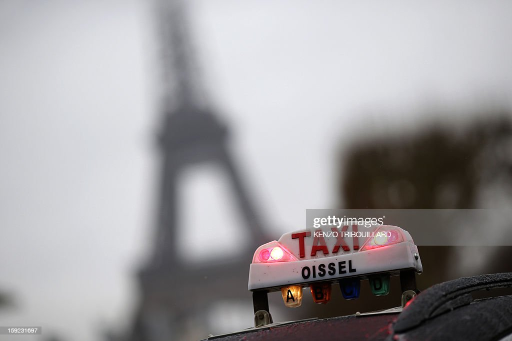 A photo taken on January 10, 2013 shows a taxi light with the Eiffel tower in the background during a nationwide demonstration in Paris to protest against legislative changes concerning the transport of sick and incapacitated passengers. AFP PHOTO / KENZO TRIBOUILLARD