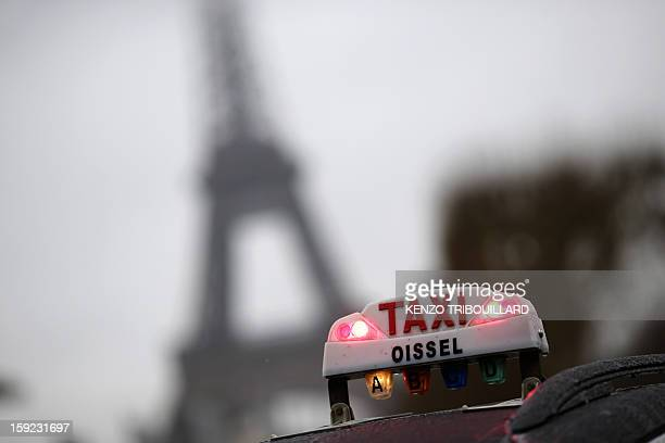 A photo taken on January 10 2013 shows a taxi light with the Eiffel tower in the background during a nationwide demonstration in Paris to protest...