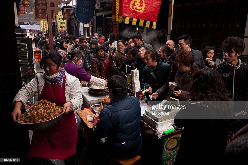 A photo taken on January 14 2011 shows people as they queue for food at a stall in Chengdu Sichuan province The capital of Sichuan Chengdu and its...