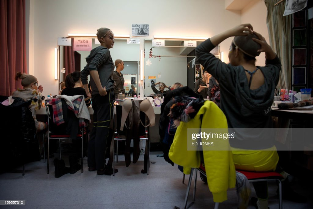 A photo taken on January 15, 2013 shows cast members applying make-up prior to a Chinese performance of 'Cats' at the Century Theatre in Beijing. Featuring a kung-fu cat, and a set design that includes bird cages and Peking duck, the culturally adapted Mandarin version of British composer Andrew Lloyd Webber's hit musical 'Cats' is hoping to bring West End success to the far east. The show, which runs until February 3, is on the final leg of a country-wide tour after passing through Shanghai, Chonqing, and Guangzhou. Western musicals have traditionally been rare in China with 'Cats' following its compatriot spectacle 'Mamma Mia!' as the country's second localised large-scale musical theatre production. AFP PHOTO / Ed Jones
