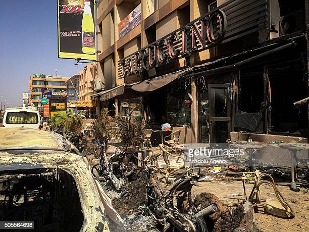 A photo taken on January 18 2016 shows the bombed car wrecks and damage outside the Cappuccino cafe in Ouagadougou following the terror attacks in...