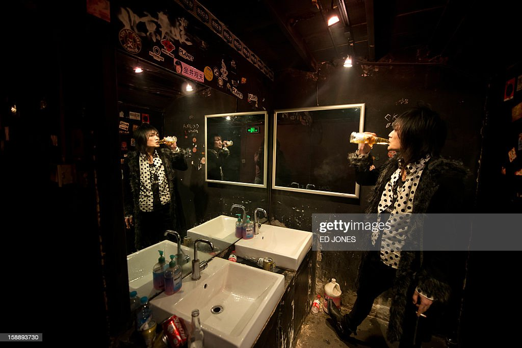 A photo taken on January 2, 2013 shows a band member of hard-rock group Los Crasher prior to their performance at the Mao Livehouse music venue in Beijing. Traditionally outcast by state radio and television, independent music acts in Beijing continue to pack out the city's many 'livehouse' venues where ear-splitting bands and hard-rocking fans represent a flourishing underground live music scene irrespective of the night of the week. However, major record deals are elusive and while available sales data is thin, bands get by on what they make from concerts and fairly low-level CD sales in a market notorious for piracy. AFP PHOTO / Ed Jones