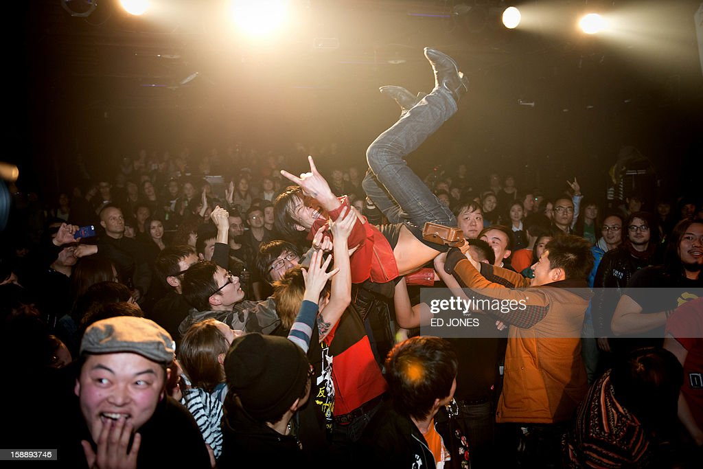 A photo taken on January 2, 2013 shows a crowd-surfer during a performance by punk band Demerit at the Mao Livehouse music venue in Beijing. Traditionally outcast by state radio and television, independent music acts in Beijing continue to pack out the city's many 'livehouse' venues where ear-splitting bands and hard-rocking fans represent a flourishing underground live music scene irrespective of the night of the week. However, major record deals are elusive and while available sales data is thin, bands get by on what they make from concerts and fairly low-level CD sales in a market notorious for piracy. AFP PHOTO / Ed Jones