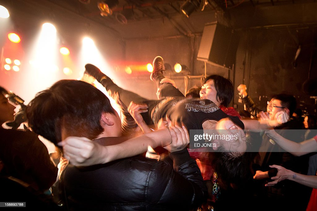 A photo taken on January 2, 2013 shows a crowd-surfer during a performance by rock band Demerit at the Mao Livehouse music venue in Beijing. Traditionally outcast by state radio and television, independent music acts in Beijing continue to pack out the city's many 'livehouse' venues where ear-splitting bands and hard-rocking fans represent a flourishing underground live music scene irrespective of the night of the week. However, major record deals are elusive and while available sales data is thin, bands get by on what they make from concerts and fairly low-level CD sales in a market notorious for piracy. AFP PHOTO / Ed Jones