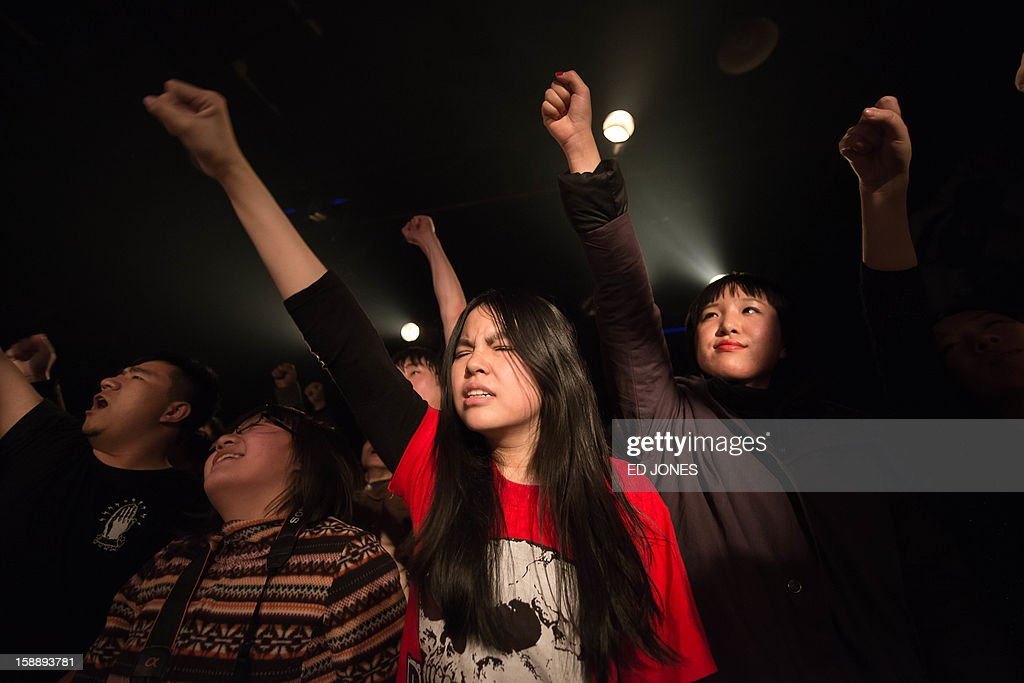 A photo taken on January 2, 2013 shows fans during a performance by punk band Demerit at the Mao Livehouse music venue in Beijing. Traditionally outcast by state radio and television, independent music acts in Beijing continue to pack out the city's many 'livehouse' venues where ear-splitting bands and hard-rocking fans represent a flourishing underground live music scene irrespective of the night of the week. However, major record deals are elusive and while available sales data is thin, bands get by on what they make from concerts and fairly low-level CD sales in a market notorious for piracy. AFP PHOTO / Ed Jones