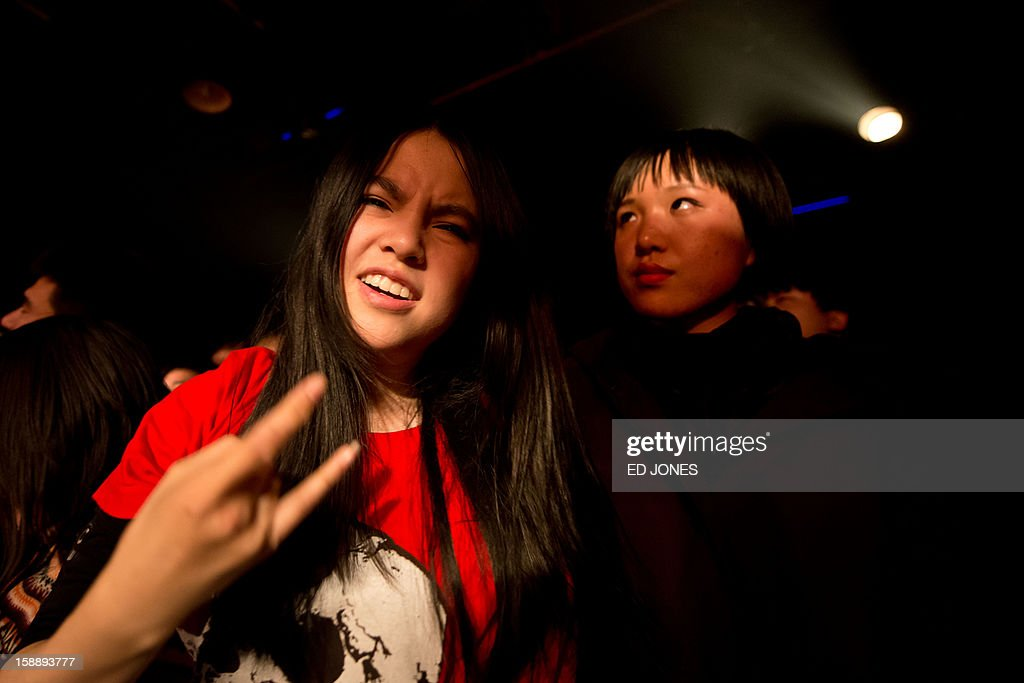 A photo taken on January 2, 2013 shows fans during performance by punk band Demerit at the Mao Livehouse music venue in Beijing. Traditionally outcast by state radio and television, independent music acts in Beijing continue to pack out the city's many 'livehouse' venues where ear-splitting bands and hard-rocking fans represent a flourishing underground live music scene irrespective of the night of the week. However, major record deals are elusive and while available sales data is thin, bands get by on what they make from concerts and fairly low-level CD sales in a market notorious for piracy. AFP PHOTO / Ed Jones