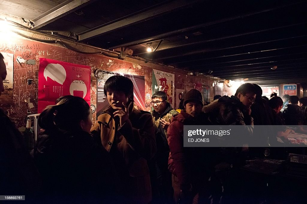 A photo taken on January 2, 2013 shows live music fans at the Mao Livehouse music venue in Beijing. Traditionally outcast by state radio and television, independent music acts in Beijing continue to pack out the city's many 'livehouse' venues where ear-splitting bands and hard-rocking fans represent a flourishing underground live music scene irrespective of the night of the week. However, major record deals are elusive and while available sales data is thin, bands get by on what they make from concerts and fairly low-level CD sales in a market notorious for piracy. AFP PHOTO / Ed Jones