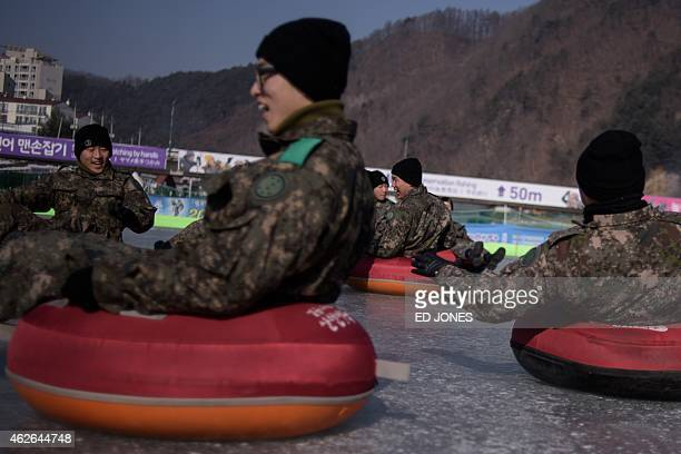 A photo taken on January 31 2015 shows a group of military service cadets riding an iceslide as they attend an annual ice fishing festival in...
