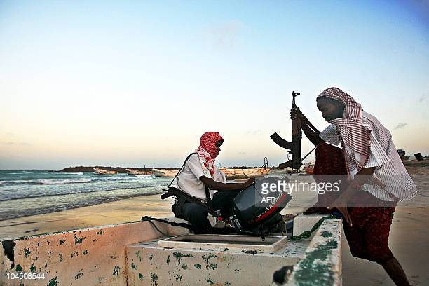 Photo taken on January 4 2010 shows armed Somali pirates carrying out preparations to a skiff in Hobyo northeastern Somalia ahead of new attacks on...