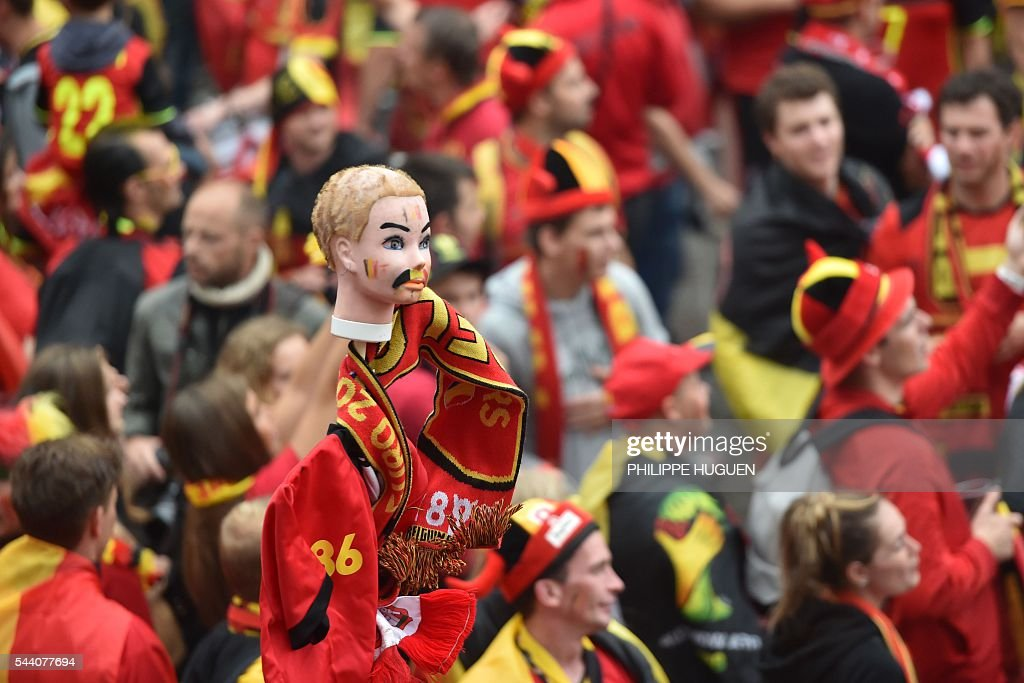 A photo taken on July 1, 2016 shows a doll head painted with Belgium's colors as Belgium's supporters wcheer their team at the main square, La Grand Place, in Lille ahead of the Euro 2016 football tournament quarter final match between Belgium and Wales. / AFP / PHILIPPE