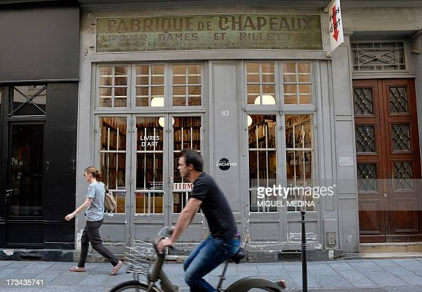 A photo taken on July 12 2013 shows people passing along a book shop of the Rue VielleduTemple street in the Marais district in the 3rd and 4th...