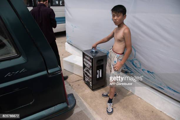 A photo taken on July 22 2017 shows a boy standing with a karaoke machine at the West Sea Barrage beach outside the coastal city of Nampho southwest...