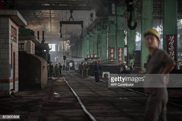 TOPSHOT A photo taken on July 22 2017 shows workers at the Chollima Steel Complex southwest of Pyongyang The Chollima Steel Complex has around 8000...