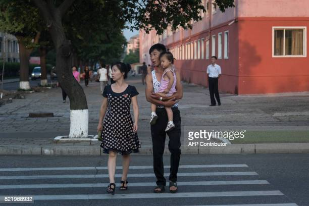 A photo taken on July 24 2017 shows a man woman and child crossing a road in Pyongyang / AFP PHOTO / Ed JONES