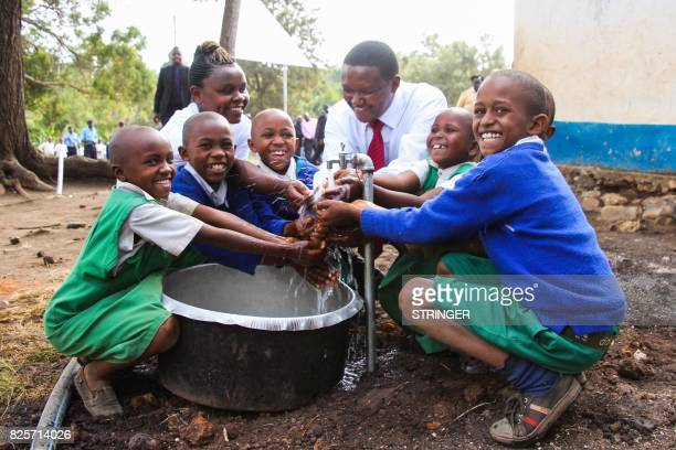 A photo taken on July 8 2015 shows the governor of Machakos Alfred Mutua washing hands with children from a borehole water tap in Machakos southern...