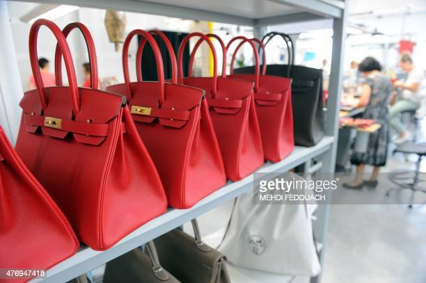 A photo taken on June 11 2015 shows Hermes Birkin bags at the Maroquinerie de la Tardoire a Hermes workshop specialized in products made with...