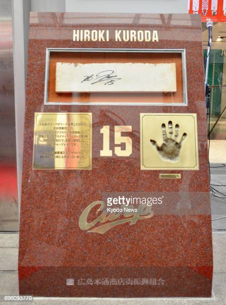 Photo taken on June 15 shows a monument to honor the achievements by former Hiroshima Carp pitcher Hiroki Kuroda installed on a local shopping street...