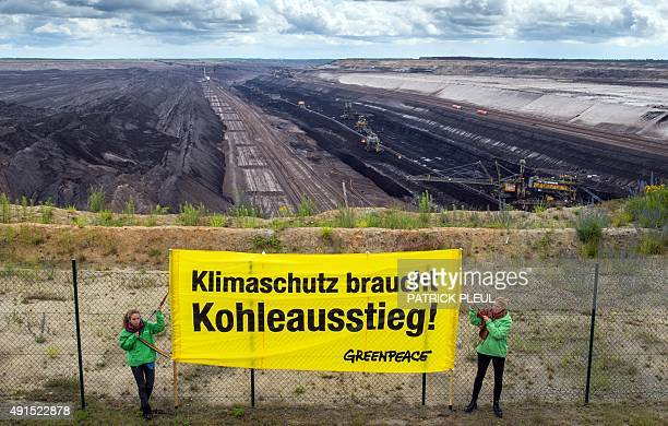 A photo taken on June 24 shows members of the environmental organization Greenpeace holding a banner reading 'Climate protection needs Coal exit' in...