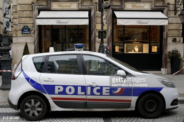 A photo taken on March 1 2016 shows a police car parked near an empty display window in the Chopard luxury jewellery store on the Place Vendome in...