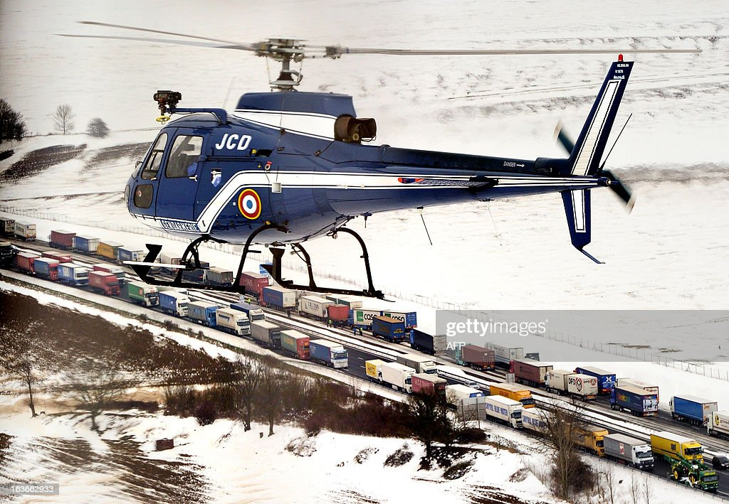 Photo taken on March 13, 2013 shows a helicopter of the French Gendarmerie patrolling above the A1 highway (Lille-Paris) around Roye, northern France, where some dozen trucks were blocked, a day after a heavy snow storm hit the area. Icy conditions caused road closures and slowdowns, in particular in the north of France, but highways were gradually opening as snowdrifts were cleared and vehicles stranded during the snowstorm were recovered.