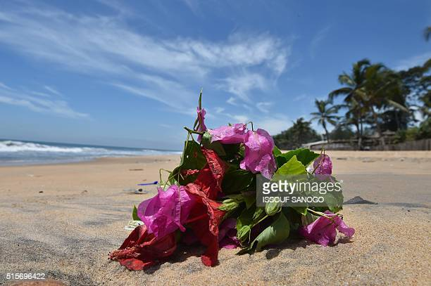 A photo taken on March 15 2016 shows flowers on the beach in GrandBassam a day after gunmen attacked the Ivory Coast resort town popular with...
