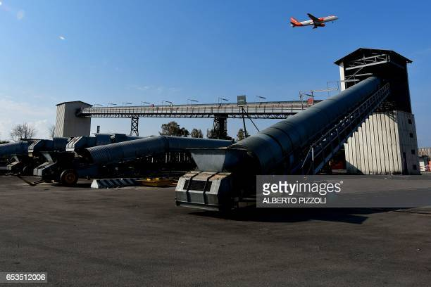A photo taken on March 15 2017 shows an EasyJet plane flying over the commercial dock of French sugar cooperative Cristal Union at the SFIR...