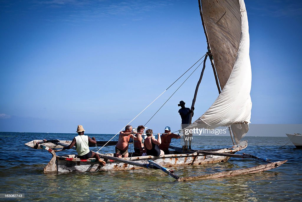 Photo taken on March 2, 2013 shows a group of tourists taking a traditional Kenyan sailing boat on an ocean cruise off Bamburi beach in the city of Mombasa. Many tourists traveling with families are confident and stay in Mombasa during the general elections taking place on March 4, 2013.