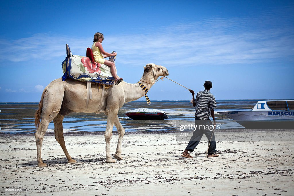 Photo taken on March 2, 2013 shows a young girl riding a camel along the Bamburi beach in the city of Mombasa. Many tourists traveling with families are confident and stay in Mombasa during the general elections taking place on March 4, 2013.