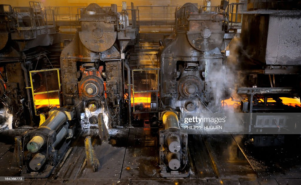 A photo taken on March 21, 2013 shows a steel coil passing through a hot wide strip mill at the Arcelor Mittal steel plant in Grande-Synthe, northern France.
