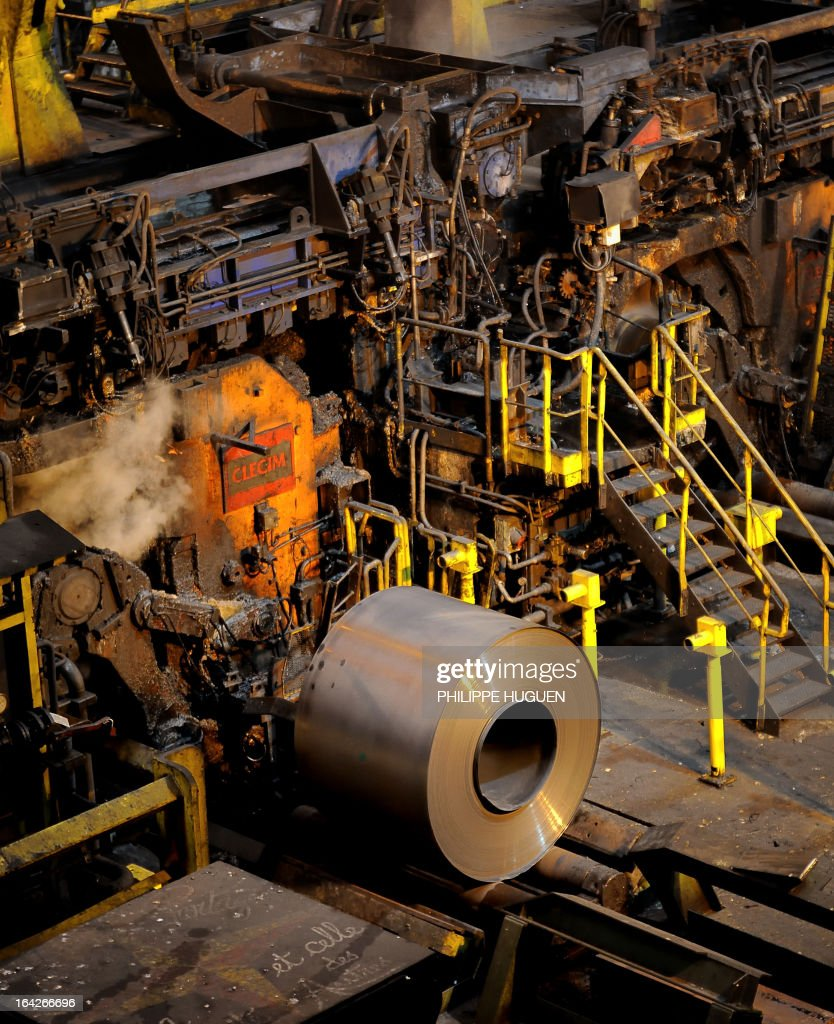 A photo taken on March 21, 2013 shows a steel rolled coil coming out of a hot wide strip mill at the Arcelor Mittal steel plant in Grande-Synthe, northern France.