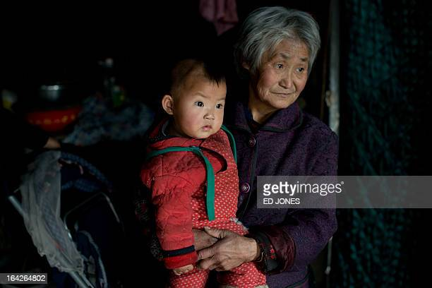 A photo taken on March 21 2013 shows a woman with one of her grandchildren in their home in Chengde Hebei province a town where inhabitants are not...