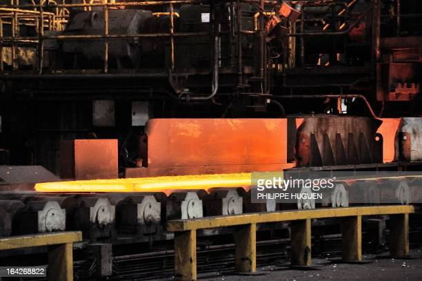 A photo taken on March 21 2013 shows hot steel coming out of a hot wide strip mill at the Arcelor Mittal steel plant in GrandeSynthe northern France...