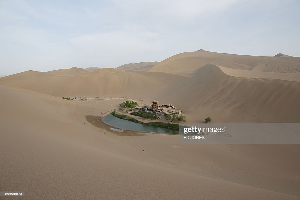 A photo taken on May 12, 2013 shows a general view of the Yueyaquan Crescent Lake in Dunhuang, in China's northwestern Gansu province. Formerly a silk route hub and centre for trade between China and the West, Dunhuang relies heavily on tourism and features a number of historic sites dating back to the Han Dynasty. The city has an arid climate and is surrounded by sand dunes, a result of increasing desertification. AFP PHOTO / Ed Jones