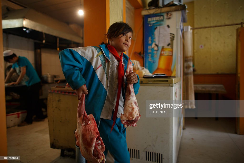 A photo taken on May 14, 2013 shows a girl carrying cuts of mutton at a halal restaurant in Jiayuguan, China's northwestern Gansu province. Cuisine in Gansu is based on the staple crops grown in the region, wheat, barley, millet, beans, sweet potatoes and is known for the Muslim restaurants known as 'qingzhen restaurants' which feature typical Chinese dishes without any pork products. AFP PHOTO / Ed Jones