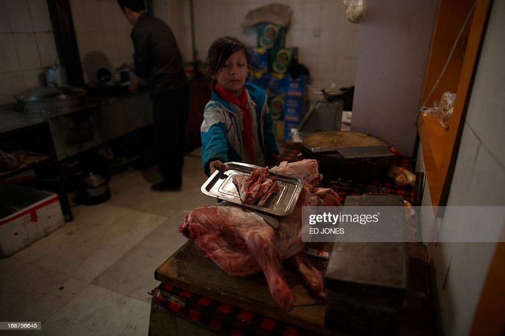 A photo taken on May 14, 2013 shows a girl holding cuts of mutton in the kitchen of a halal restaurant in Jiayuguan, China's northwestern Gansu province. Cuisine in Gansu is based on the staple crops grown in the region, wheat, barley, millet, beans, sweet potatoes and is known for the Muslim restaurants known as 'qingzhen restaurants' which feature typical Chinese dishes without any pork products. AFP PHOTO / Ed Jones