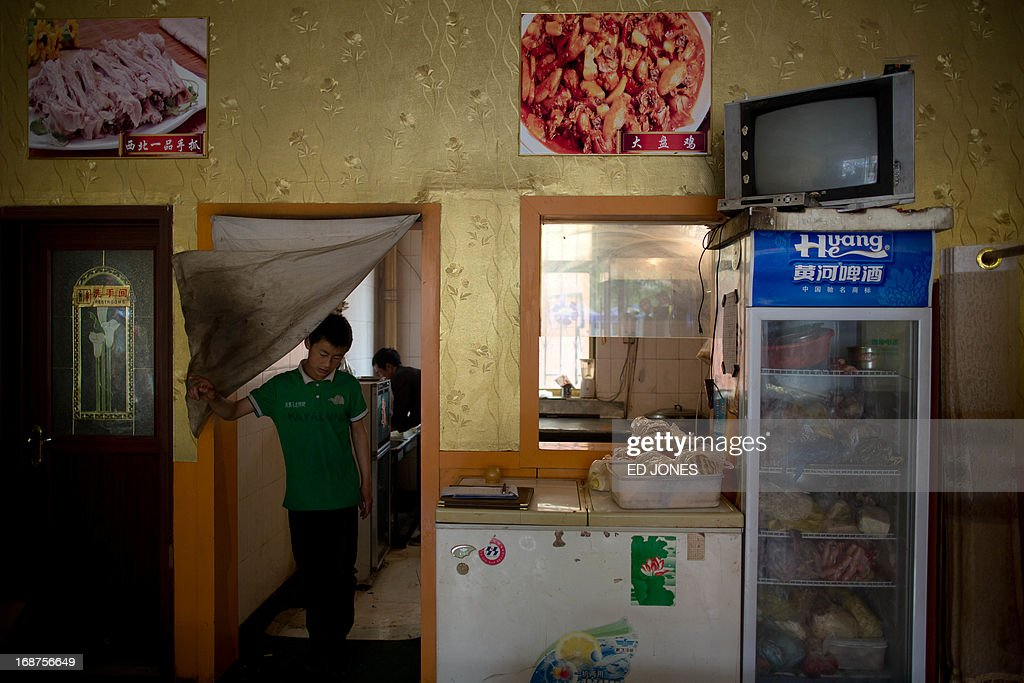 A photo taken on May 14, 2013 shows a waiter leaving the kitchen of a halal restaurant in Jiayuguan, China's northwestern Gansu province. Cuisine in Gansu is based on the staple crops grown in the region, wheat, barley, millet, beans, sweet potatoes and is known for the Muslim restaurants known as 'qingzhen restaurants' which feature typical Chinese dishes without any pork products. AFP PHOTO / Ed Jones