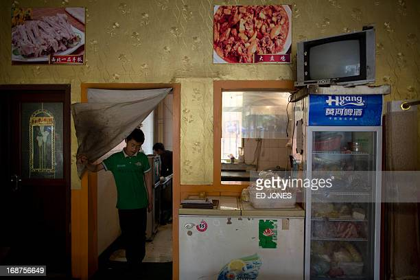 A photo taken on May 14 2013 shows a waiter leaving the kitchen of a halal restaurant in Jiayuguan China's northwestern Gansu province Cuisine in...