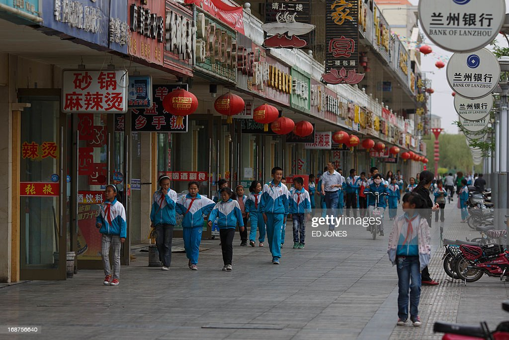 A photo taken on May 14, 2013 shows school children walking past halal restaurants on a street in Jiayuguan, China's northwestern Gansu province. Cuisine in Gansu is based on the staple crops grown in the region, wheat, barley, millet, beans, sweet potatoes and is known for the Muslim restaurants known as 'qingzhen restaurants' which feature typical Chinese dishes without any pork products. AFP PHOTO / Ed Jones