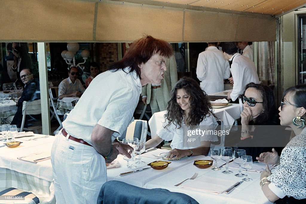 A photo taken on May 16, 1988 shows German actor Klaus Kinski, flanked with his wife Deborah (C), lunching during the 41th Cannes International Film Festival.