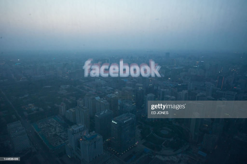 A photo taken on May 16, 2012 shows a computer screen displaying the logo of social networking site Facebook reflected in a window before the Beijing skyline. With investors hungry for Facebook shares ahead of a hotly anticipated offering, the social network unveiled a 25 percent increase in the number of shares to be sold at the market debut. AFP PHOTO / Ed Jones