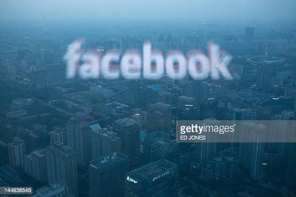 A photo taken on May 16 2012 shows a computer screen displaying the logo of social networking site Facebook reflected in a window before the Beijing...