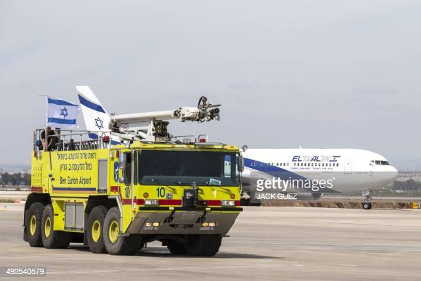 A photo taken on May 19 2014 shows a fire engine driving past an ElAl airways Boeing 700300 ER on the runway at Israel's Ben Gurion International...