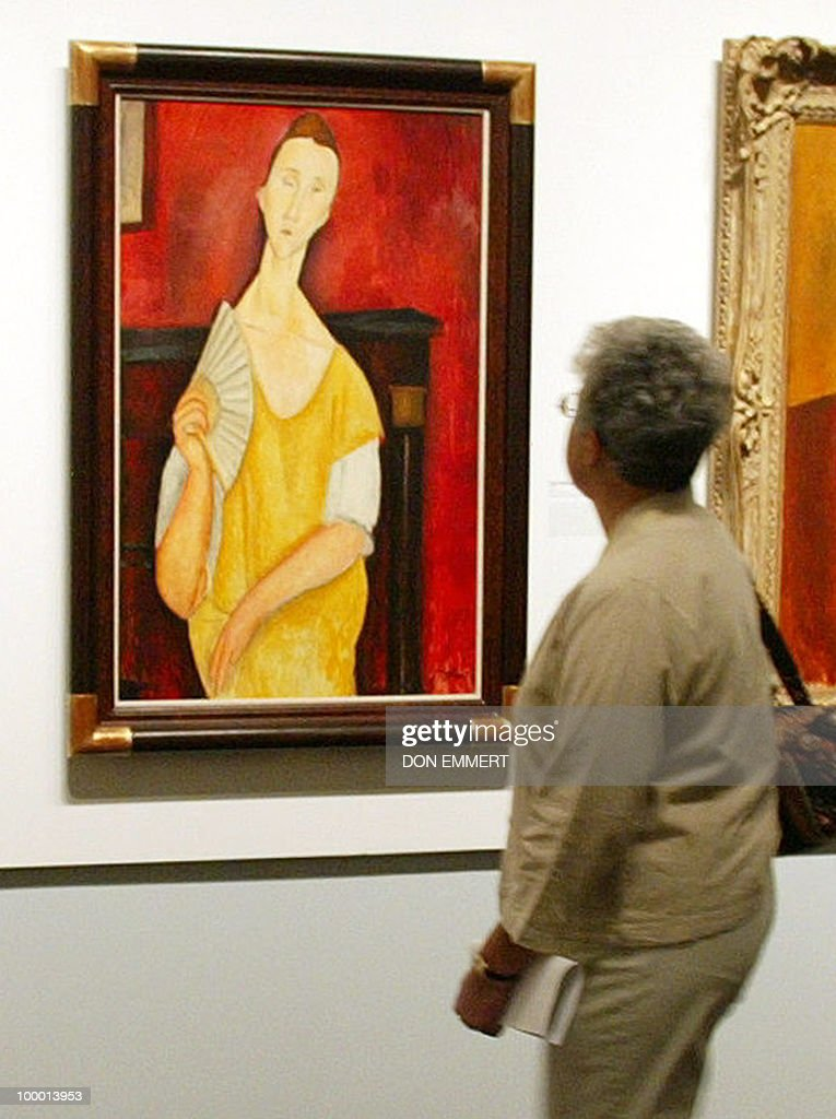 A photo taken on May 21, 2004 shows a visitor looking at the painting 'La Femme à l'éventail' (Woman with a Fan) by Amedeo Modigliani during an exhibition at The Jewish Museum in New York. Five works including Modigliani's painting 'Woman with a Fan' were discovered missing on May 20, 2010 at the Paris Musee d'Art Moderne (Modern Art Museum). The stolen paintings included Picasso's cubist 'Pigeon aux petits pois' (Dove with Green Peas), which the Spanish artist created in 1912, and his French contemporary Matisse's 'La pastorale' (Pastoral) from 1905. AFP PHOTO/Don EMMERT