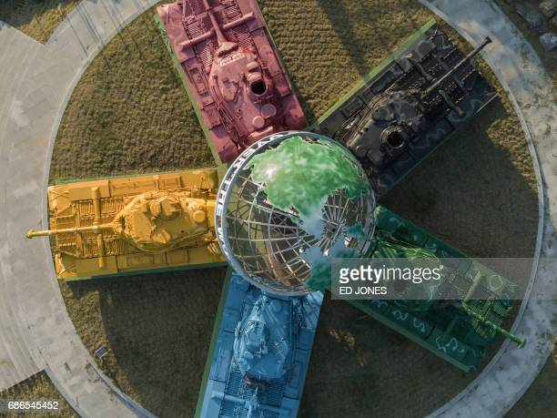 A photo taken on May 21 2017 shows an aerial view of an art installation featuring Korean warera tanks painted in different colours around a globe...