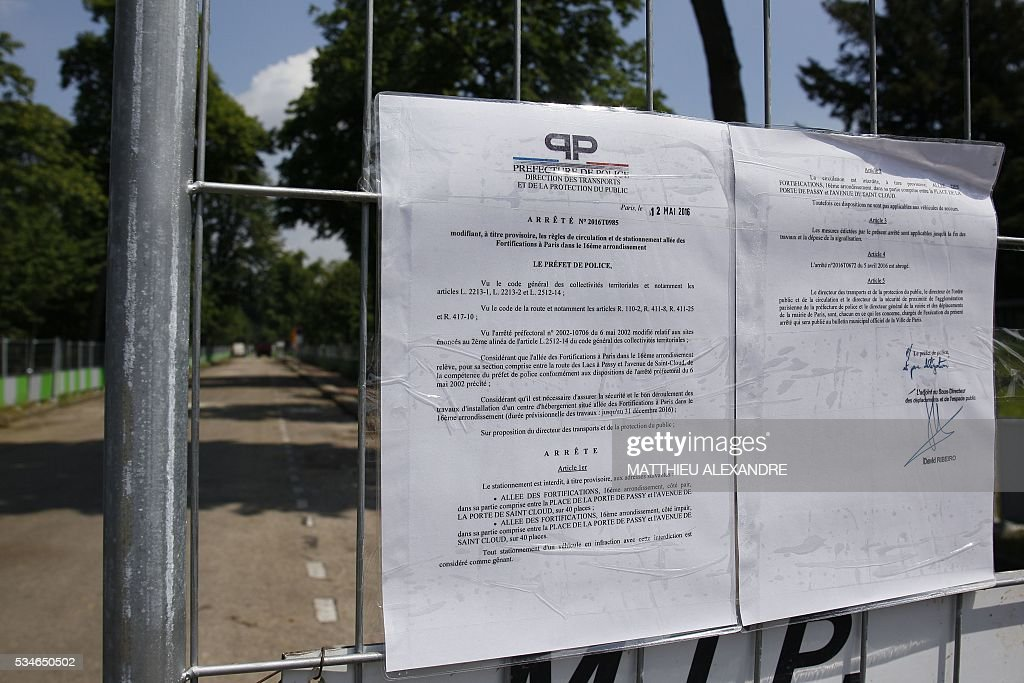 A photo taken on May 27, 2016 in Paris shows a document from the Paris Police Prefecture on the construction site of a futur shelter for migrants on the edge of the Bois de Boulogne in the 16th arrondissement of the French capital. Six pre-fabricated wooden structures in the chic 16th that will house 200 homeless people. / AFP / MATTHIEU