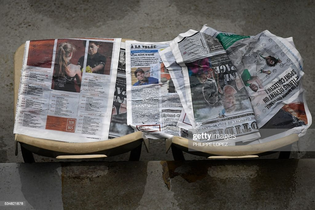 A photo taken on May 28, 2016 shows rain soaked copies of the Roland Garros newspaper 'Quotidien' as rain interrupts play during the women's third round match between the US's Venus Williams and France's Alize Cornet at the Roland Garros 2016 French Tennis Open in Paris. / AFP / PHILIPPE